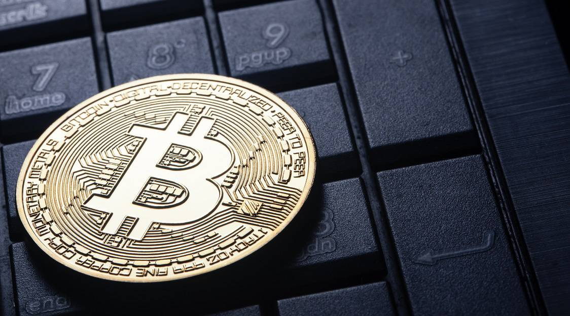 Virtual currency is the golden bitcoin on the computer keyboard. The concept of virtual business and currency.